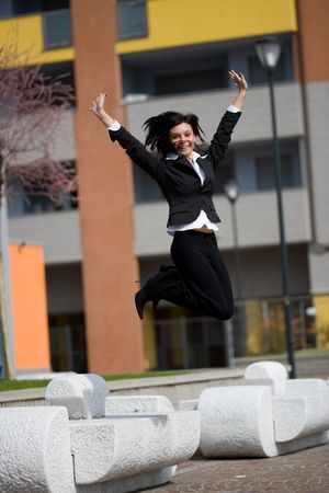 strenght: full figure with jump of a young adult businesswoman outdoors in a sunny day