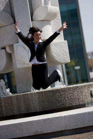 trustable: en cifras con salto de un adulto joven empresaria al aire libre en un d�a soleado  Foto de archivo