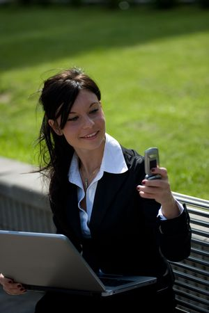 young businesswoman working outdoors at the laptop and making a phone call Stock Photo - 3016393