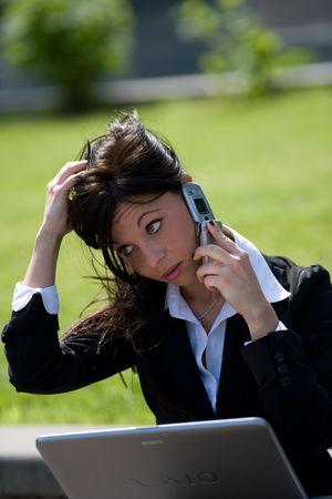 trustable: retrato de una joven empresaria hacer una llamada telef�nica con un m�vil y de trabajo con un ordenador port�til  Foto de archivo