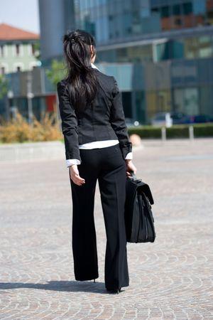 trustable: vista posterior de una joven mujer de negocios van a la oficina