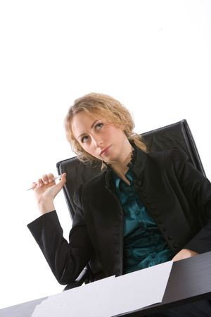 young businesswoman seated at her desk thinking photo
