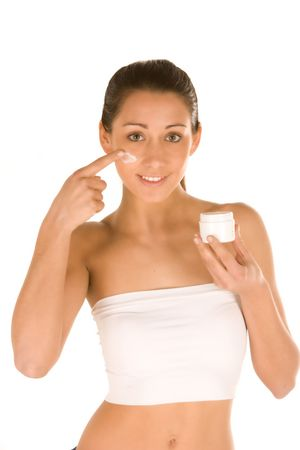 nice attractiveyoung caucasian brunette applying cream on the face isolated on white.Concept of skincare Stock Photo - 4798727