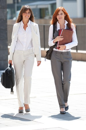 two young adult caucasian businesswoman walking outdoors watching in camera Stock Photo - 7917387