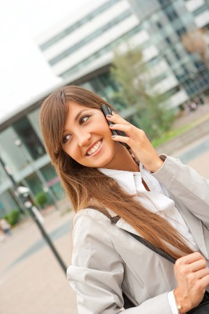 young caucasian businesswoman makes a phone call outdoors photo