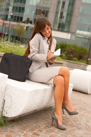 young adult caucasian businesswoman making a phone calls outdoors,seated and taking notes photo