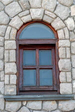 Arched wooden window, on a stone wall, with rusticated glass
