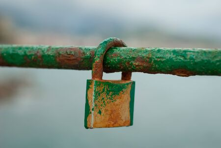 Old padlock, a sign of love, attached to a marine railing, worn by salt