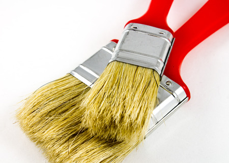 housebuilding: two red paint brushes isolated on white Stock Photo