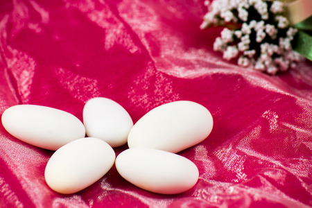 sugared almonds: five white sugared almonds on pink background Stock Photo