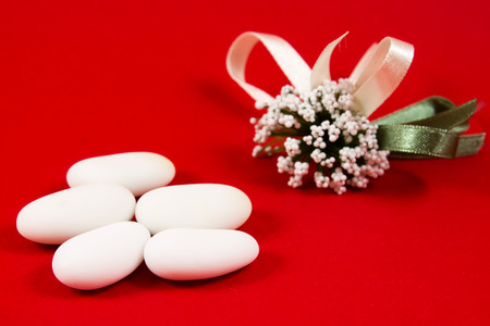 sugared: five white sugared almonds on red background
