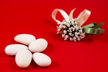 sugared almonds: five white sugared almonds on red background