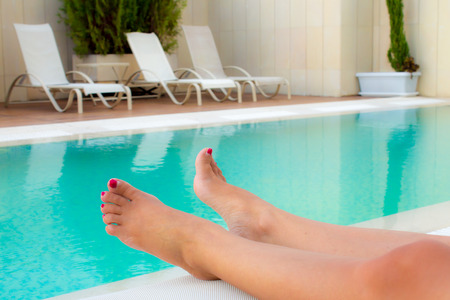 a bathing place: tanned legs of woman in the pool