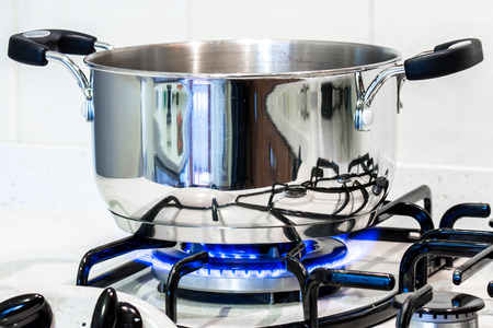 cook with a steel pot on the stove in the kitchen