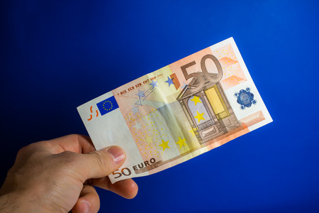 lend a hand: hand give money on a blue background Stock Photo
