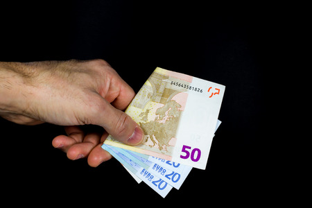 lend a hand: hand holding out some banknotes, on a dark background