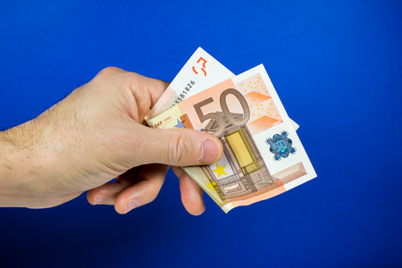 lend a hand: hand holding out a bill, on a blue background Stock Photo