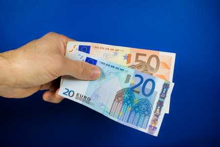lend a hand: hand holding out two banknotes, on a blue background