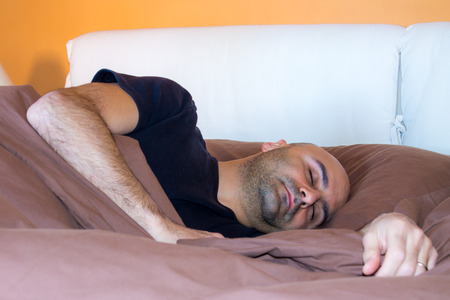 bald man: tired man with a beard who sleeps in bed Stock Photo