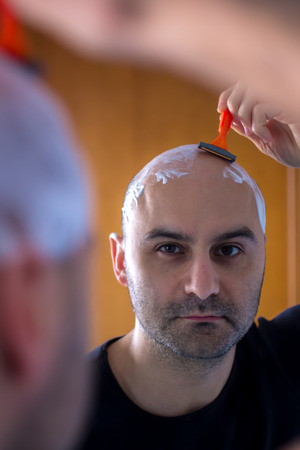 skinhead: man who shaves his head with a razor reflected in the mirror Stock Photo