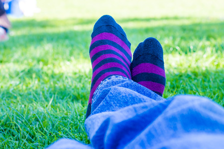 closeup of colored socks of a teenager who is resting in a park