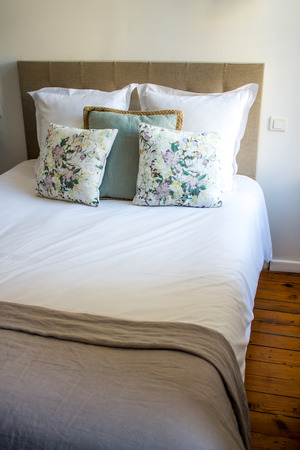 bedspread: Soft white and colored pillows on a comfortable bed