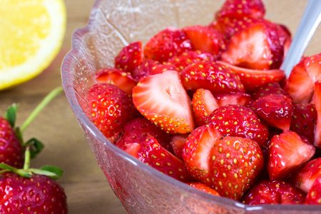 woden: a cup of sliced strawberries with lemon in a woden table