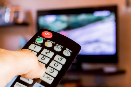 channel surfing: Use the remote control to change channels on Television Stock Photo