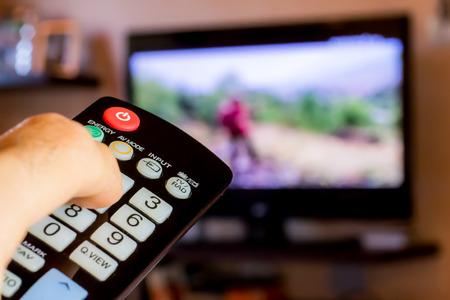 Gebruik de afstandsbediening om de kanalen op televisie te veranderen Stockfoto