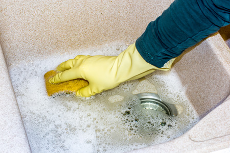 granite kitchen: housewife clean the kitchen granite sink with a sponge Stock Photo