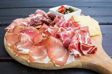 typical Italian appetizer with salami, cheese and pickles in a wooden cutting board