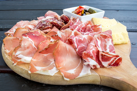 appetizers: typical Italian appetizer with salami, cheese and pickles in a wooden cutting board