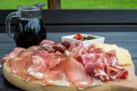 meat dish: typical Italian appetizer with salami, cheese and pickles in a wooden cutting board