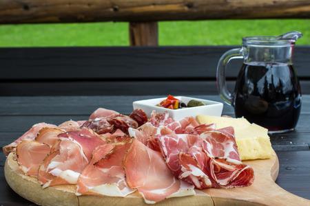 jamon y queso: típico aperitivo italiano con salami, queso y pepinillos en una tabla de madera