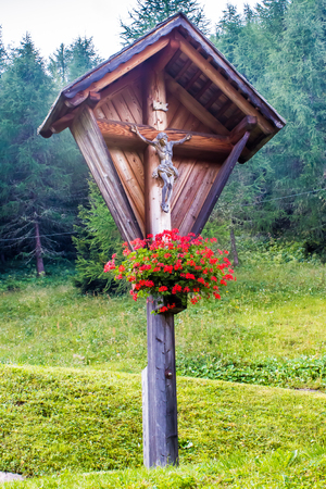 crucify: Typical wooden wayside cross near a forest in the Alps Stock Photo