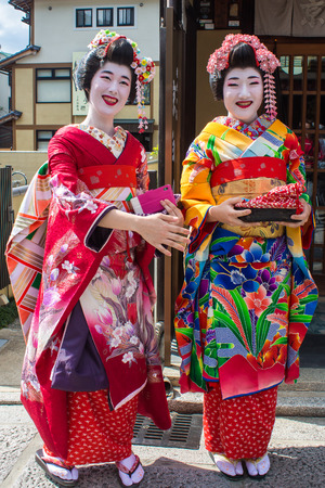 maiko: KYOTO, JAPAN - OCTOBER 14, 2015 : portrait of two smiling Maiko, Apprentices geisha, in Kyoto, Japan. Editorial