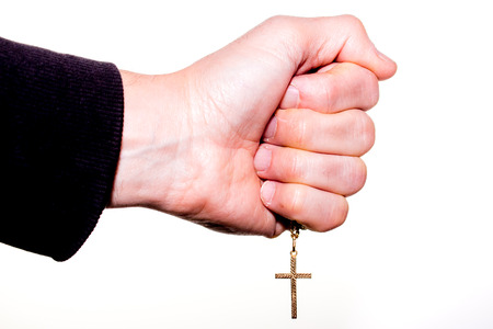 christian religion: Hand holds a chain with gold crucifix, isolated on white