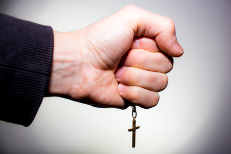 sacerdote: La mano sostiene una cadena con crucifijo de oro, aislado en blanco Foto de archivo