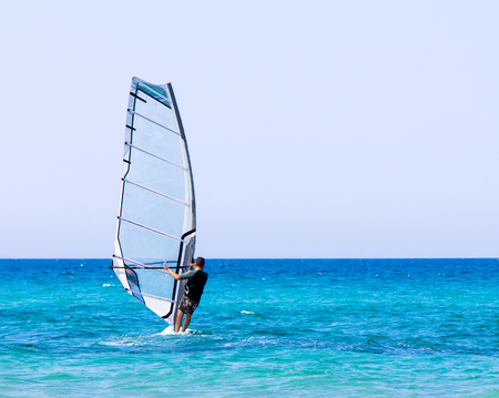 conquering: A man on windsurf conquering the waves