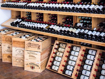 Saint Emilion, FRANCE - APRIL 13, 2015 - wooden racks with red wine bottles in a shop