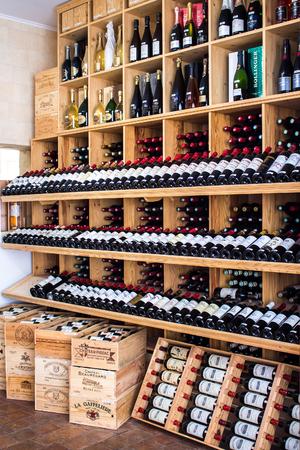 Saint Emilion, FRANCE - APRIL 13, 2015 - wooden racks with red wine bottles in a shop Editorial