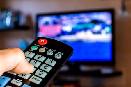 channel surfing: Hand hold the remote control to change channels on Tv