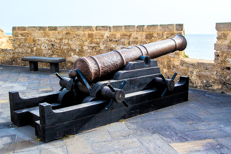 heritage protection: old bronze cannon pointing to the sea from an embrasure