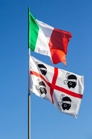 moors: The Italian national flag and that of the region of Sardinia with the four Moors, waving together in the blue sky