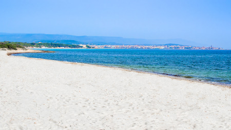 the bay of Alghero, with the white beach and the city in the background, in Sardinia, Italy