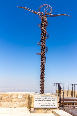 Het koperen serpentmonument op de berg Nebo in Jordanië: een kronkelig kruisbeeld, symbolisch voor de bronzen slang die door Mozes en het kruis werd geschapen waarop Jezus werd gekruisigd
