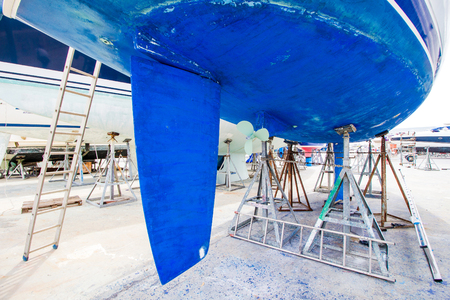 boat with blue hull in maintenance at the shipyard Imagens