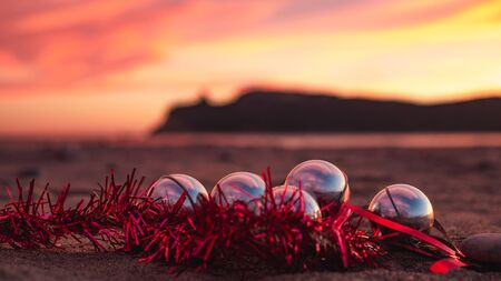 Golden hour sunset picture if Christmas decorations on the beach of Poetto, Sardinia, Italy.