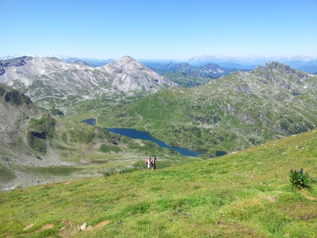 Hikers on mountain lake with a wide view at summit