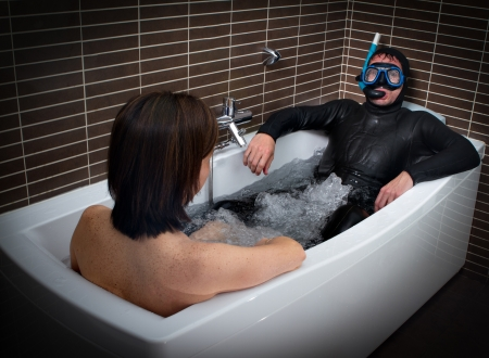 normal woman and crazy diver in a bathtub Stock Photo